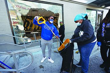 Community members clean up broken glass at McDonalds on 52nd Street in West Philadelphia, Sunday, June 1, 2020